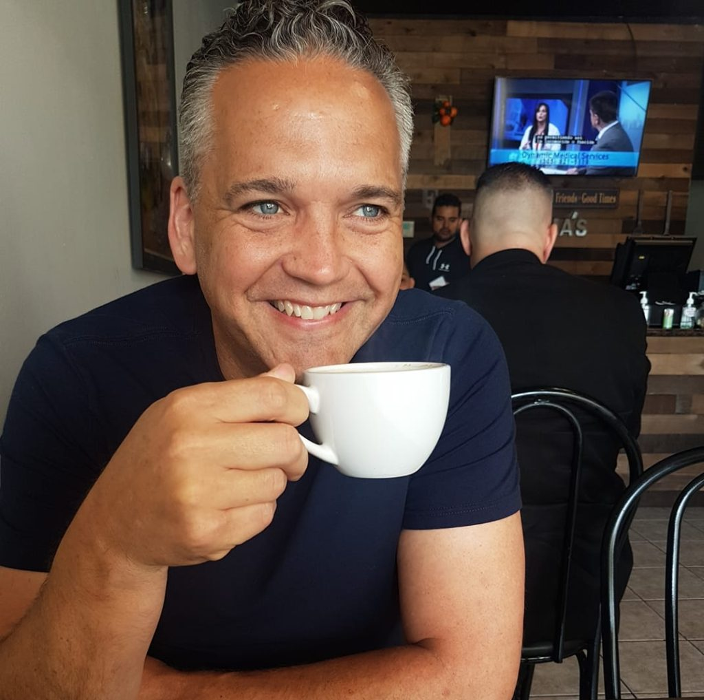Patrick W is happy holding a coffee