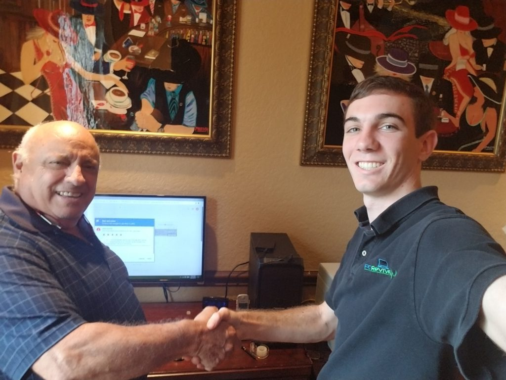 Evan Otis is shaking hands with a client after a completed computer repair