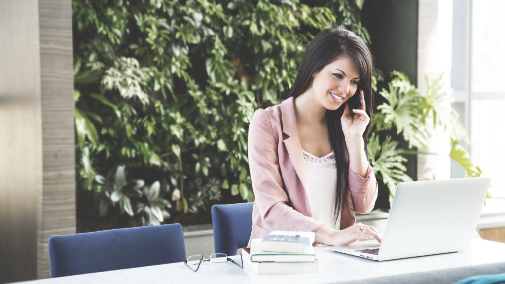 Girl talking on the phone in front of a laptop on a desk